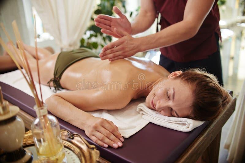 Усмехаясь женщина наслаждаясь массажем в КУРОРТЕ стоковая фотография