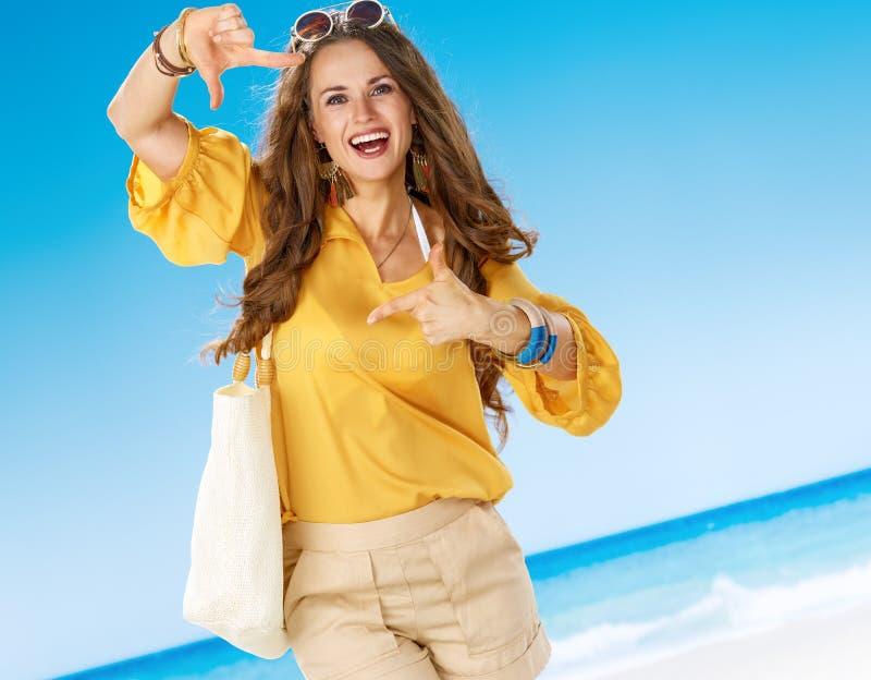 Усмехаясь женщина на береге моря обрамляя с руками стоковая фотография rf