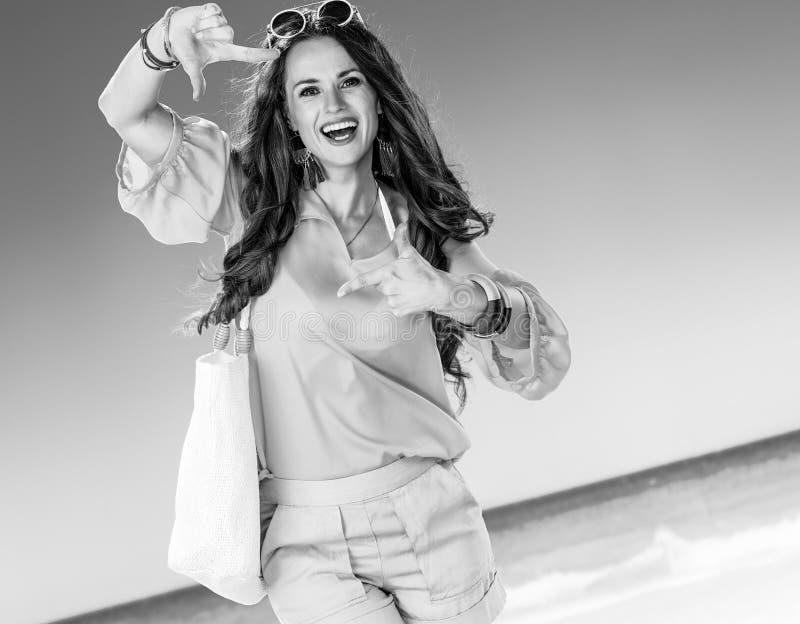 Усмехаясь женщина на береге моря обрамляя с руками стоковая фотография