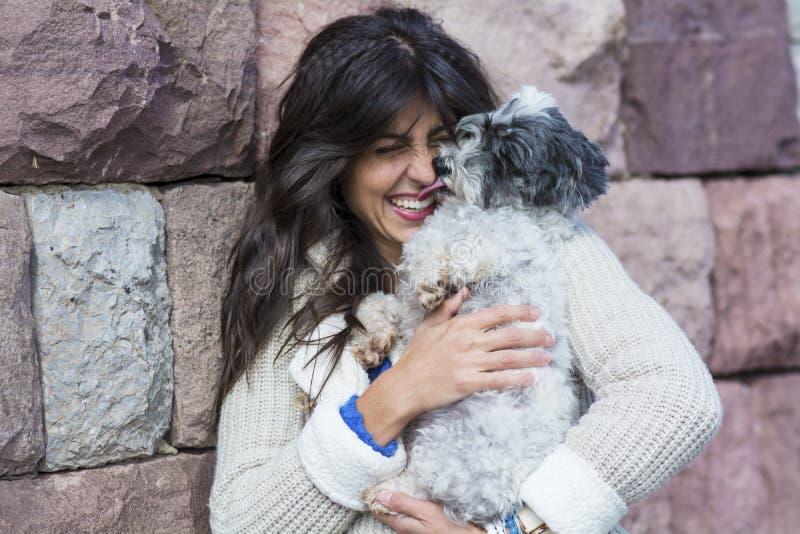 усмехаясь женщина обнимая ее белую собаку внешнюю стоковые фотографии rf
