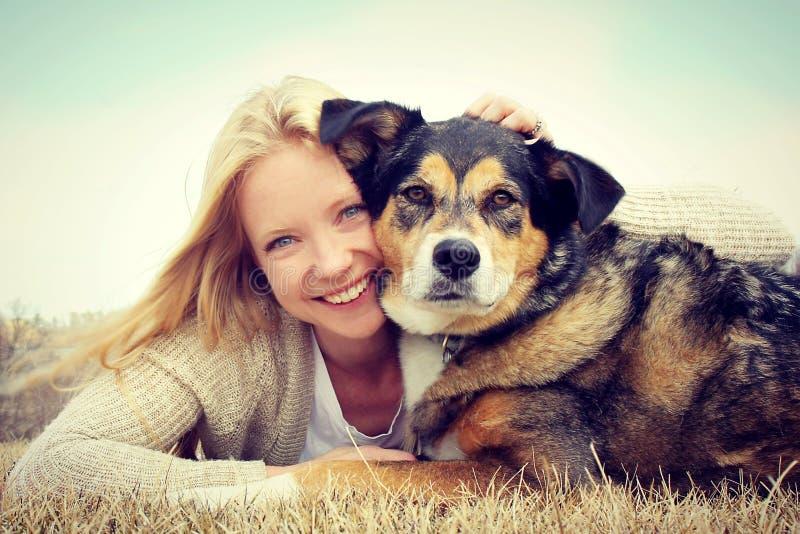 Усмехаясь женщина обнимая собаку немецкой овчарки стоковые фото