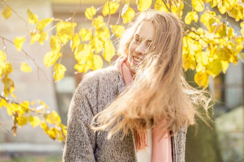Усмехаясь женщина осени держа желтый кленовый лист Милая романтичная девушка в парке падения стоковые изображения rf