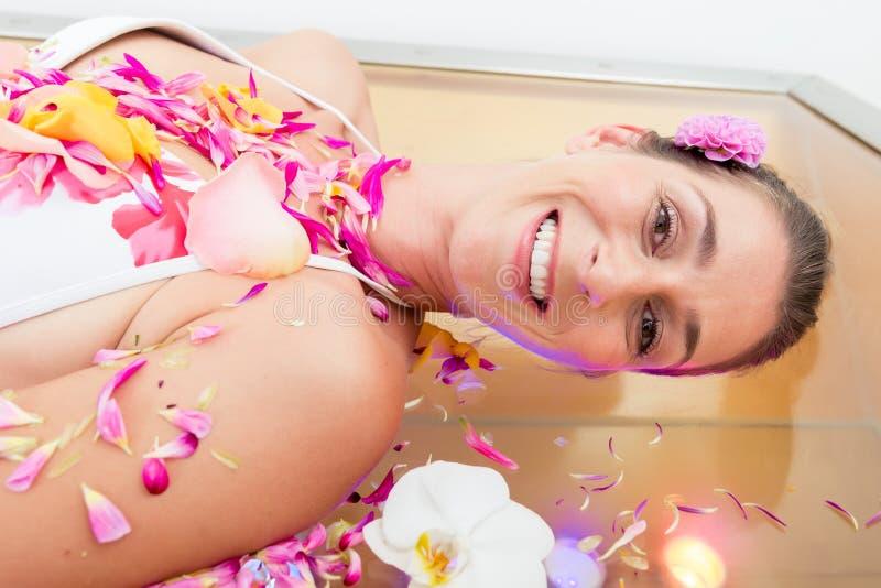 Усмехаясь женщина ослабляя во спа стоковое изображение rf