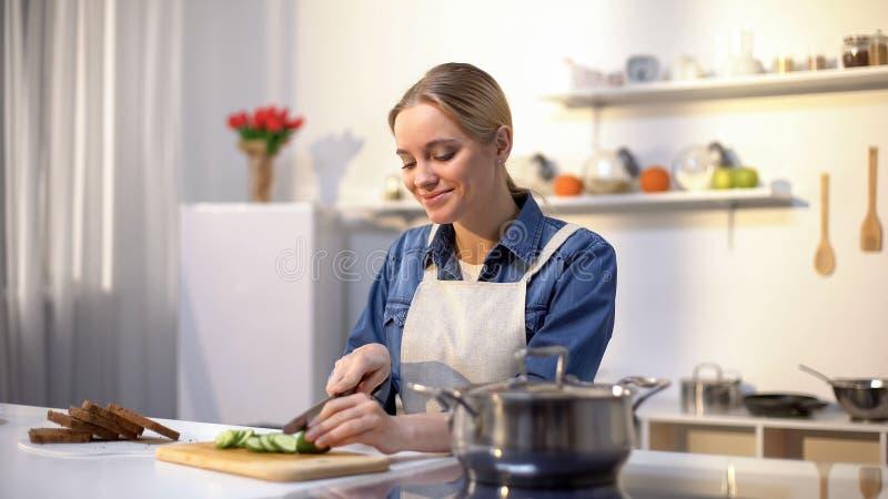Усмехаясь женщина отрезая огурец в кухне, подготавливая здоровый низко--caloried салат стоковое фото rf