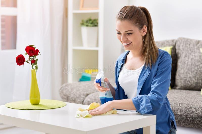 Усмехаясь женщина очищая таблицу стоковое фото