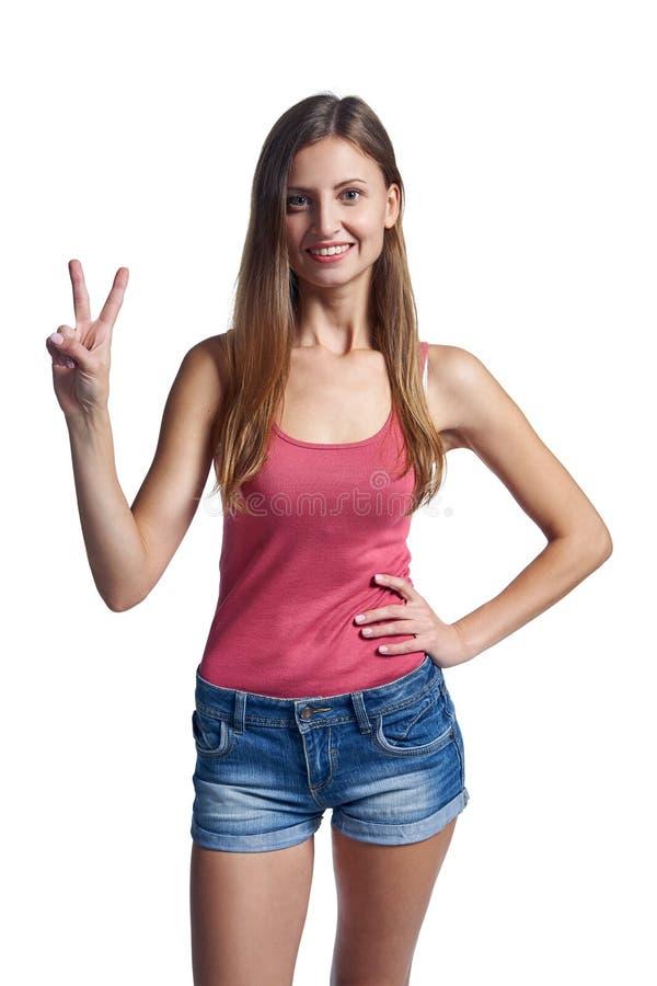 Усмехаясь женщина показывая 2 пальца, v знак стоковые фотографии rf