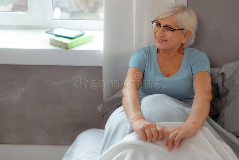Усмехаясь женщина полагаясь на стене пока сидящ в кровати стоковое изображение