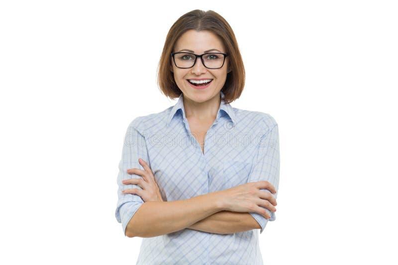 Усмехаясь женщина постаретая серединой с сложенными оружиями на белой изолированной предпосылке, стоковое фото rf