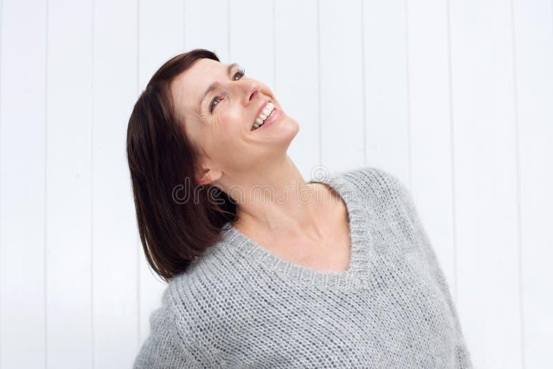 Усмехаясь женщина постаретая серединой смотря вверх стоковое изображение