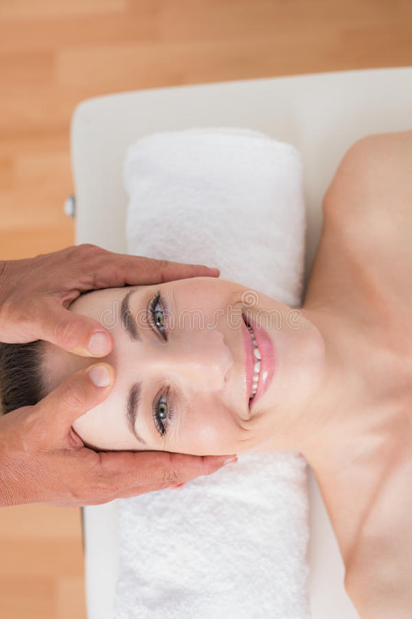 Усмехаясь женщина получая головной массаж стоковые изображения