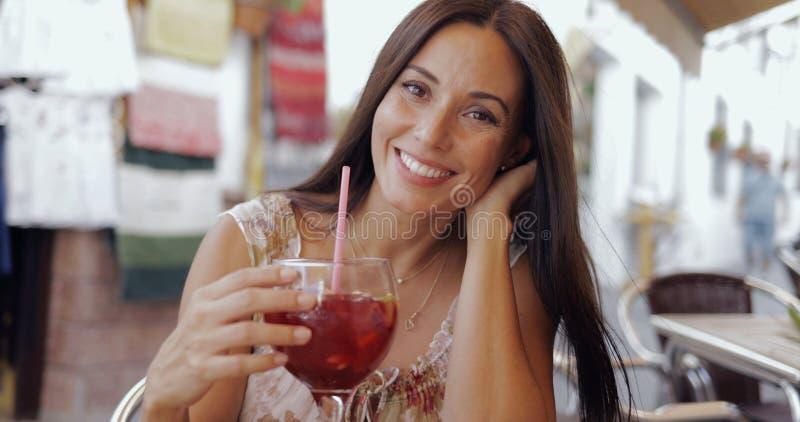 Усмехаясь женщина представляя с питьем в кафе стоковое фото rf