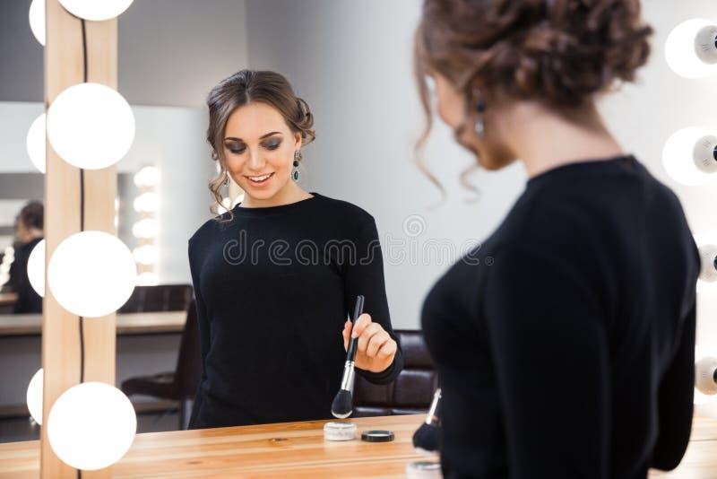 Усмехаясь женщина прикладывая косметику с щеткой стоковое изображение