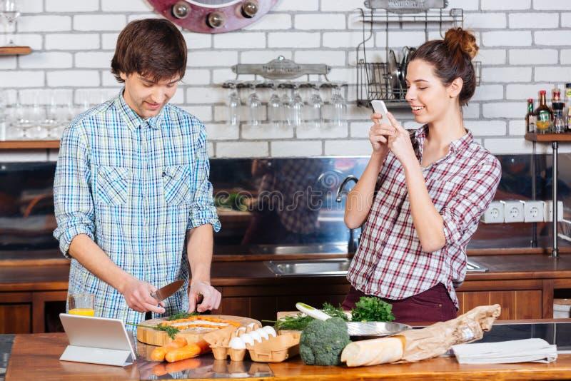 Усмехаясь женщина принимая фото ее супруга на кухне стоковые изображения rf
