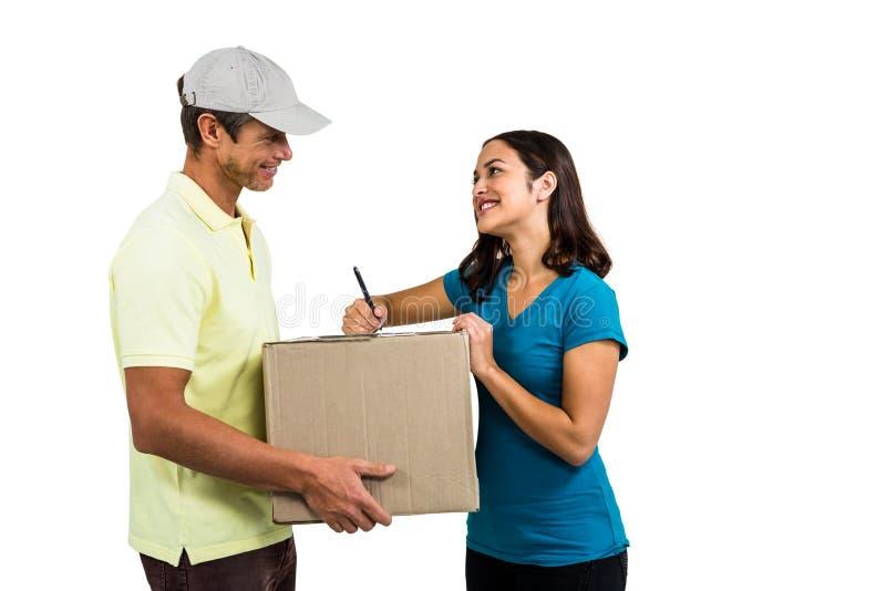 Усмехаясь женщина при работник доставляющий покупки на дом держа картонную коробку стоковые фотографии rf