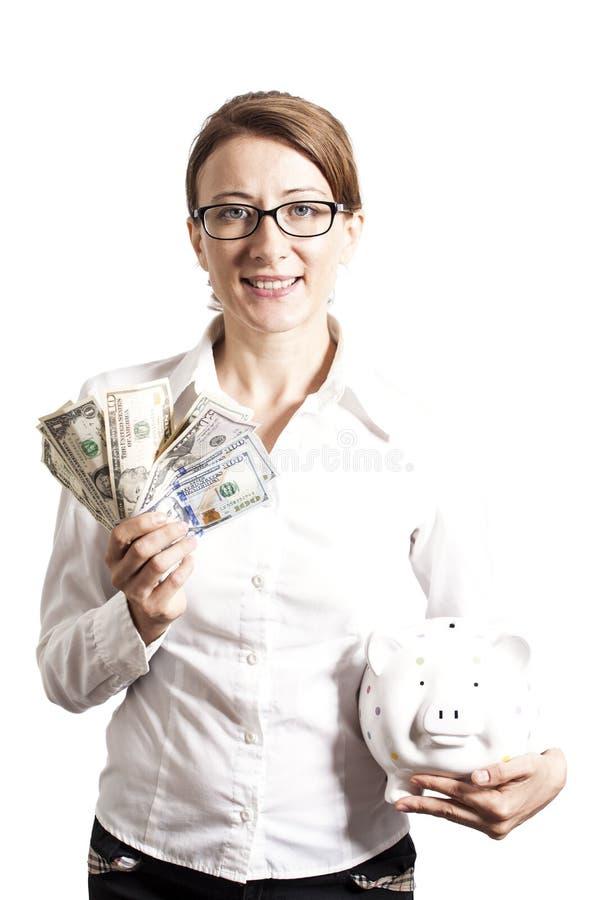 Усмехаясь женщина при eyeglasses держа копилку и доллары стоковое фото
