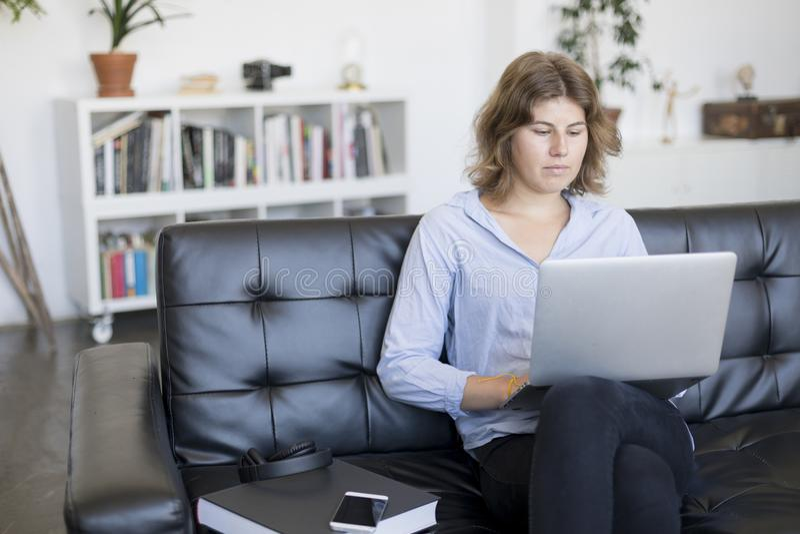 Усмехаясь женщина сидя на софе дома используя компьтер-книжку стоковые фото