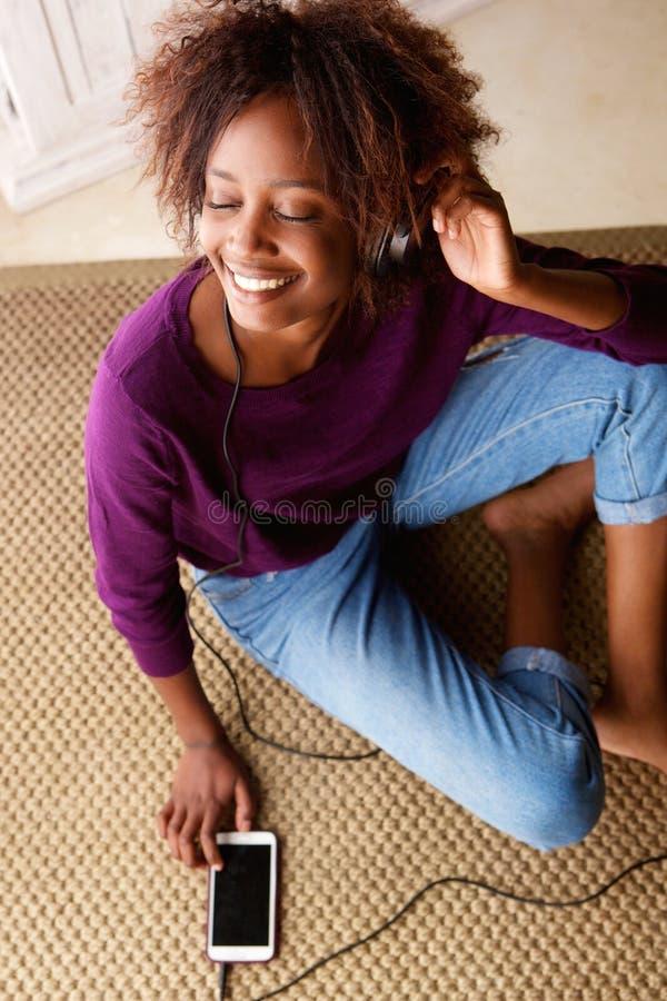 Усмехаясь женщина сидя на поле слушая к музыке на наушниках стоковое фото