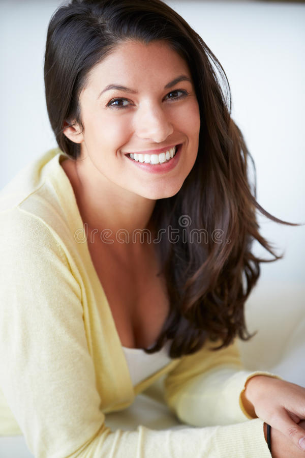 Усмехаясь женщина сидя на софе стоковое фото