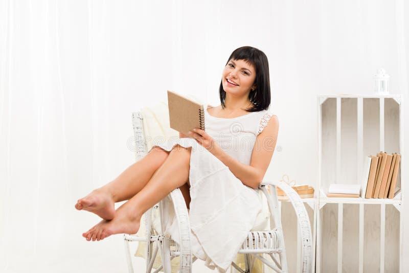 Усмехаясь женщина сидя на стуле и записи стоковое изображение