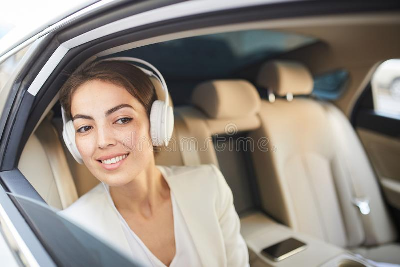 Усмехаясь женщина слушая музыку в автомобиле стоковая фотография rf
