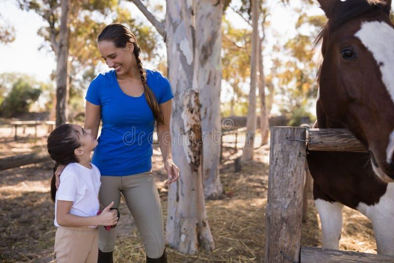 Усмехаясь женщина смотря девушку стоковое фото rf