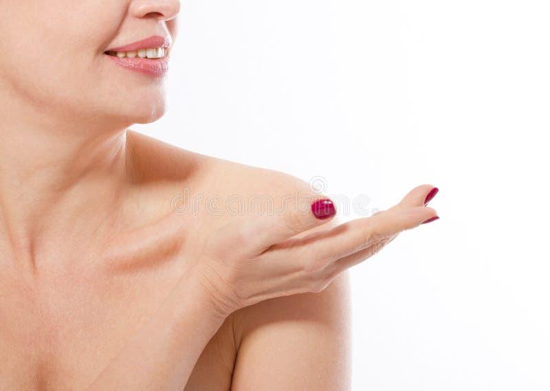 Усмехаясь женщина среднего возраста показывая место для рекламировать ее изолированной рукой на белой предпосылке Коллаген и анти стоковое изображение rf