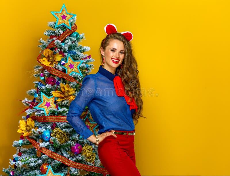 Усмехаясь женщина стоя близко рождественская елка на желтой предпосылке стоковое фото
