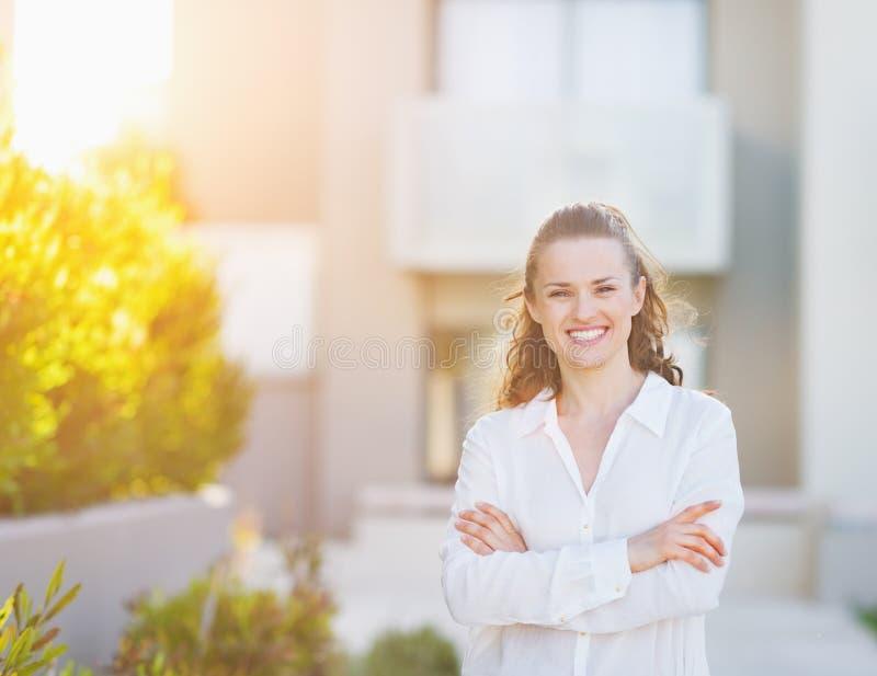 Усмехаясь женщина стоя перед жилищным строительством стоковые изображения rf