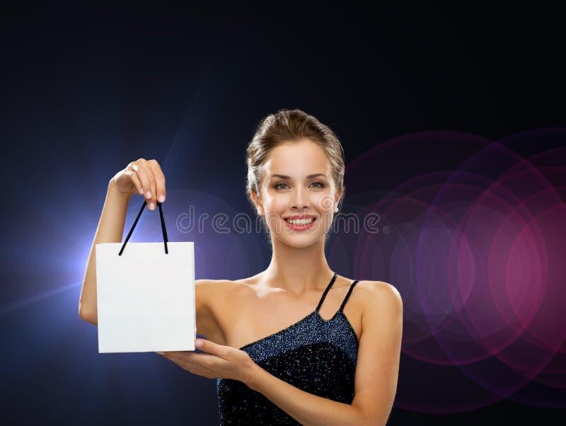 Усмехаясь женщина с белой пустой хозяйственной сумкой стоковые фотографии rf