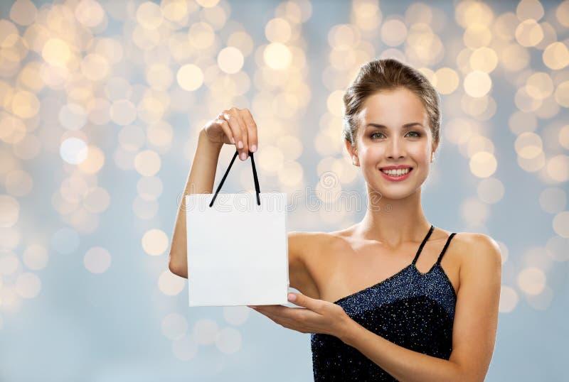 Усмехаясь женщина с белой пустой хозяйственной сумкой стоковая фотография