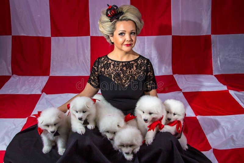 Усмехаясь женщина с белыми щенятами стоковое изображение