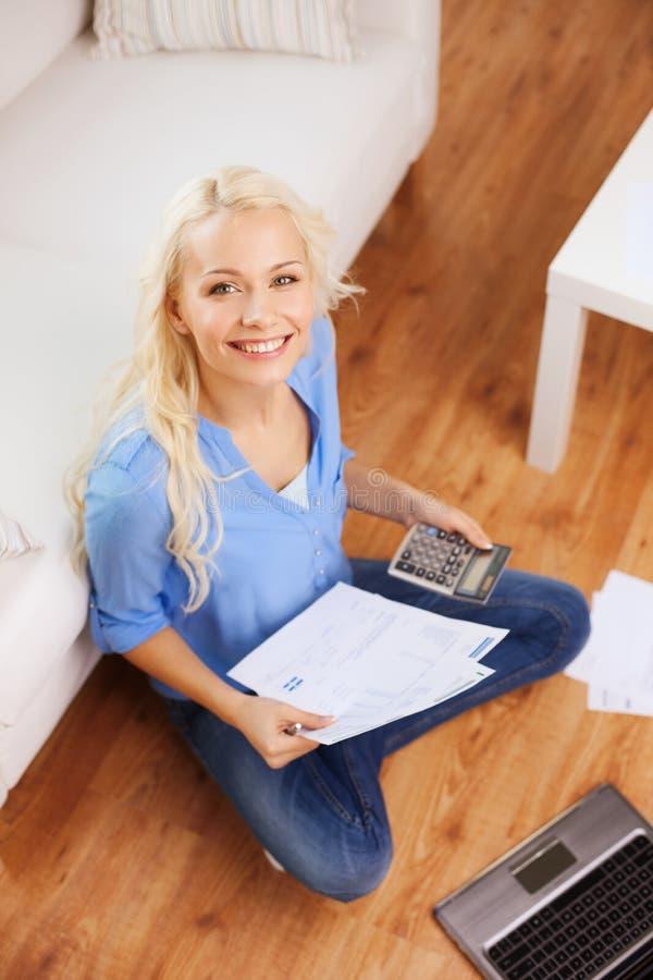 Усмехаясь женщина с бумагами, компьтер-книжкой и калькулятором стоковая фотография rf
