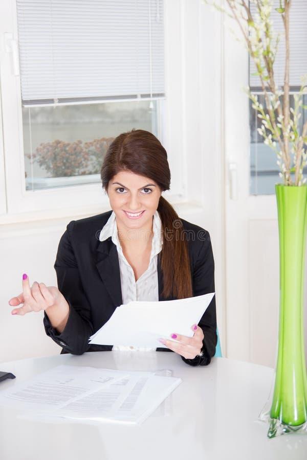 Усмехаясь женщина с бумагами на таблице стоковое фото