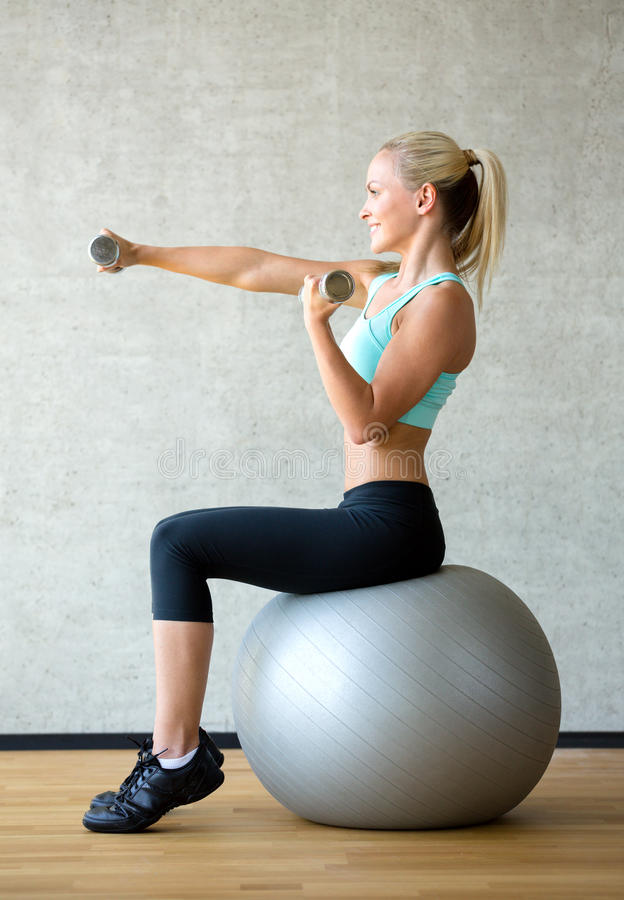 Усмехаясь женщина с гантелями и шариком тренировки стоковые изображения