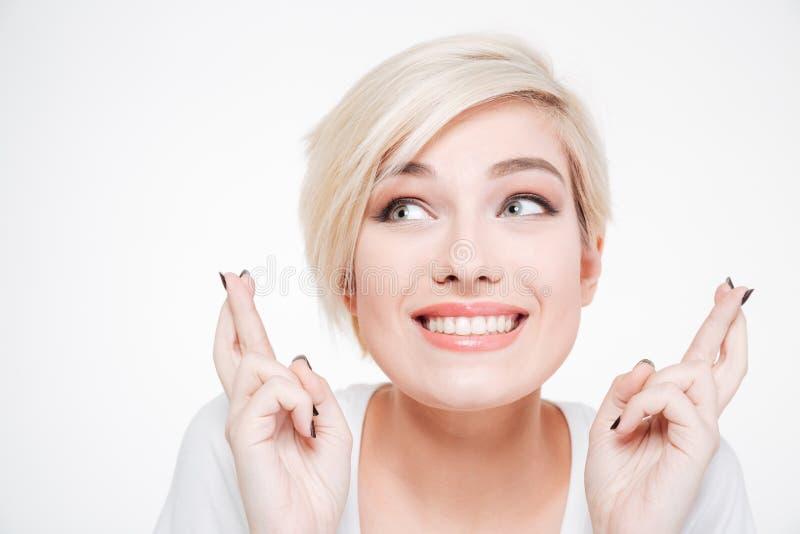 Усмехаясь женщина с жестом пересеченным пальцами стоковое изображение