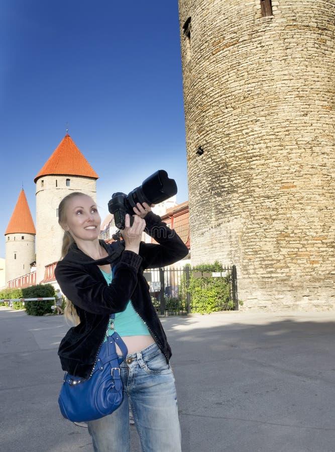 Усмехаясь женщина с камерой фотографирует старые башни стены города эстония tallinn стоковые фотографии rf