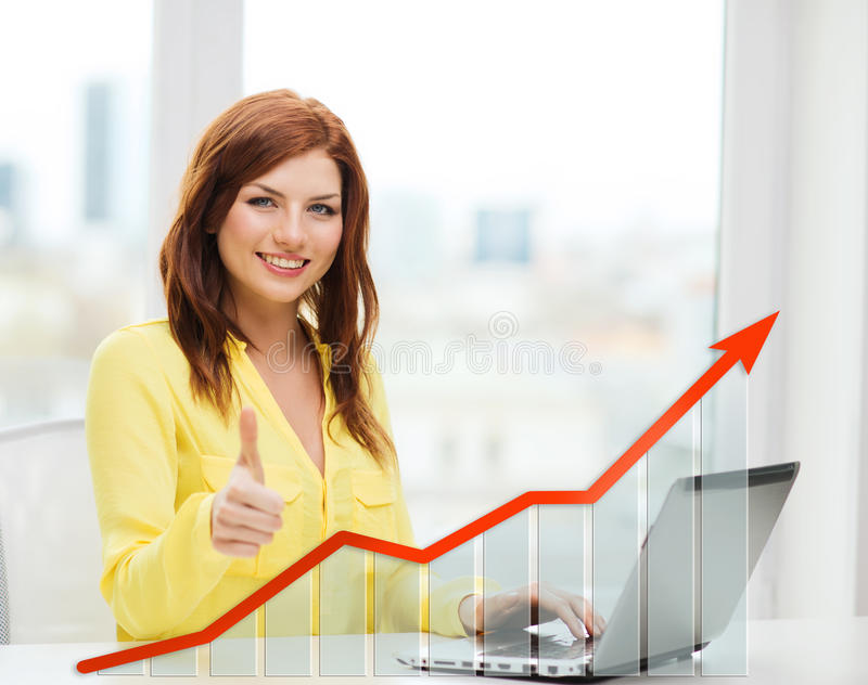 Усмехаясь женщина с компьтер-книжкой и диаграммой роста стоковое фото