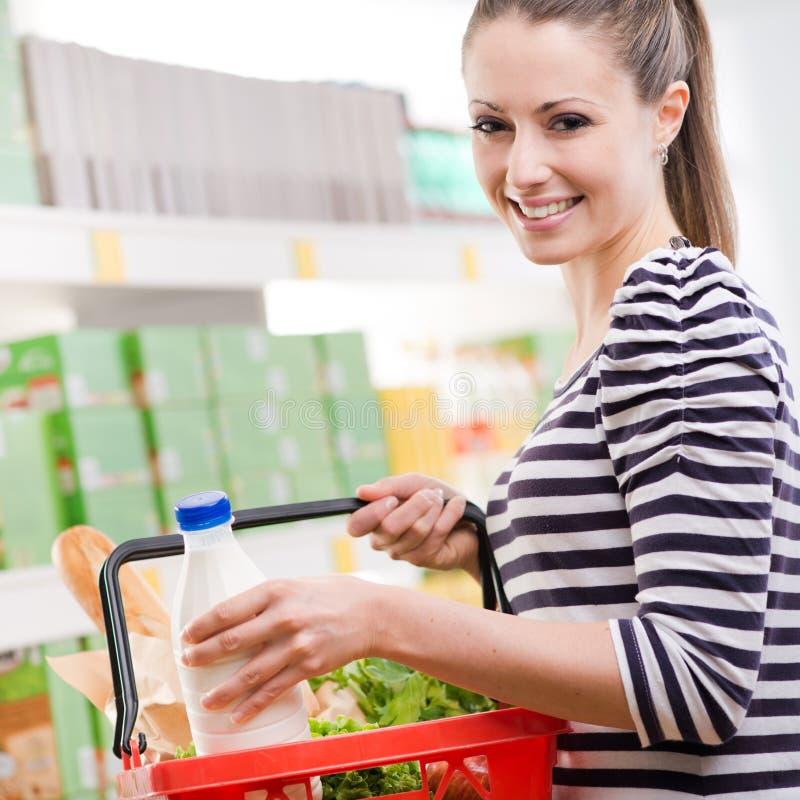 Усмехаясь женщина с корзиной для товаров стоковая фотография rf