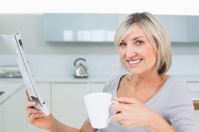 Усмехаясь женщина с кофейной чашкой и газетой в кухне стоковое фото rf