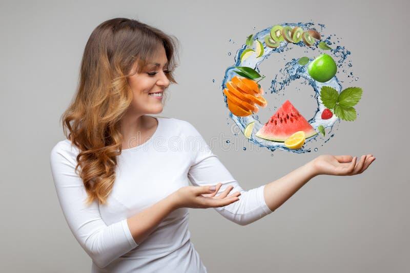 Усмехаясь женщина с плодоовощами и выплеском воды стоковое изображение rf