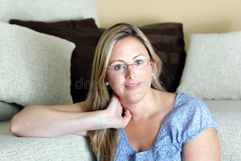 Усмехаясь женщина с рукой в голове сидя на живущей комнате стоковая фотография rf
