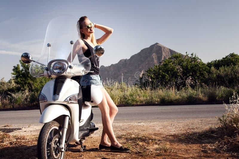 Усмехаясь женщина с самокатом Фото лета стоковые изображения rf