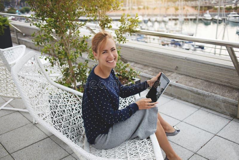 Усмехаясь женщина с сенсорной панелью в руках смотрит камеру, пока сидит outdoors около порта Марины стоковые изображения