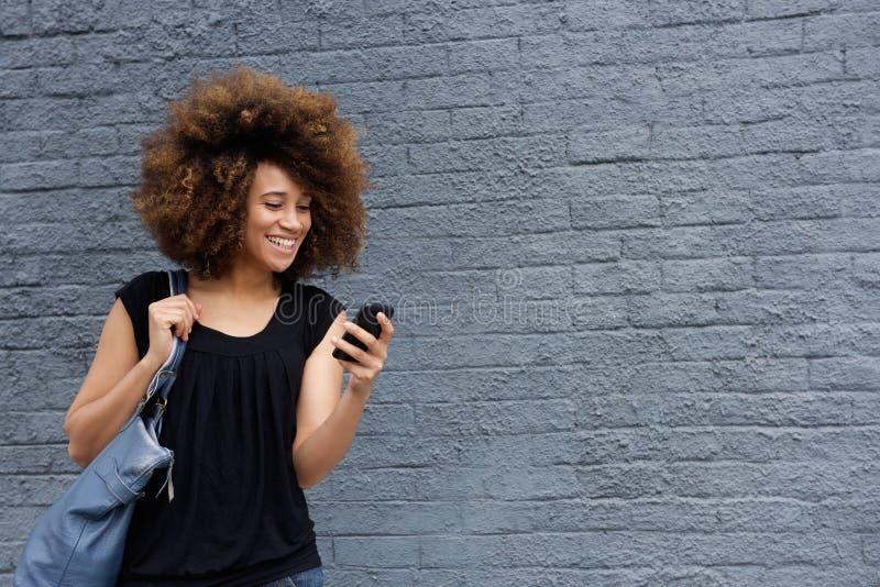 Усмехаясь женщина с сотовым телефоном стоковое фото rf