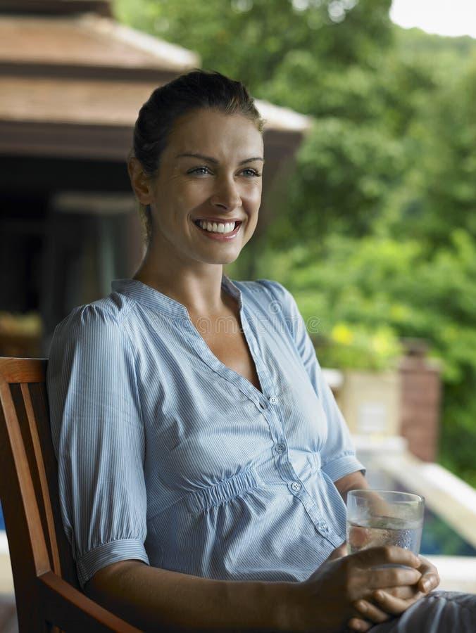 Усмехаясь женщина с стеклом воды стоковое фото rf