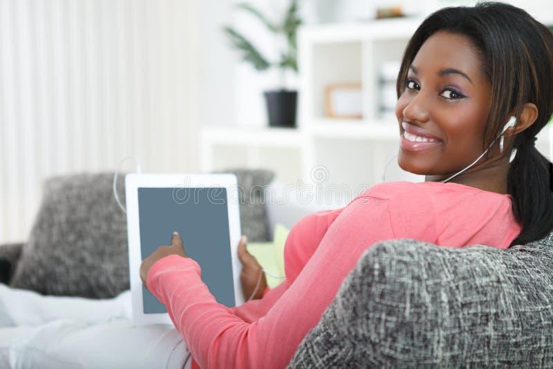 Усмехаясь женщина указывая в таблетку стоковое фото