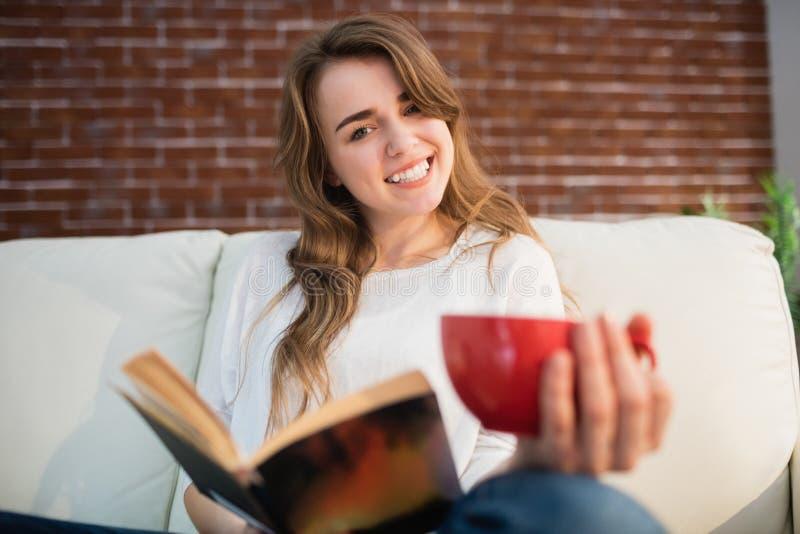 Усмехаясь женщина читая книгу пока выпивающ стоковое изображение rf