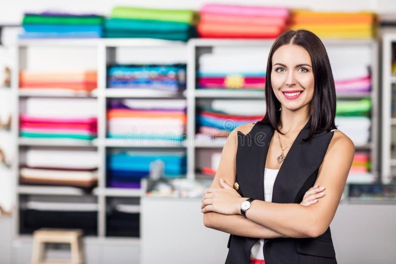 Усмехаясь женщина dressmaker в студии стоковое изображение rf