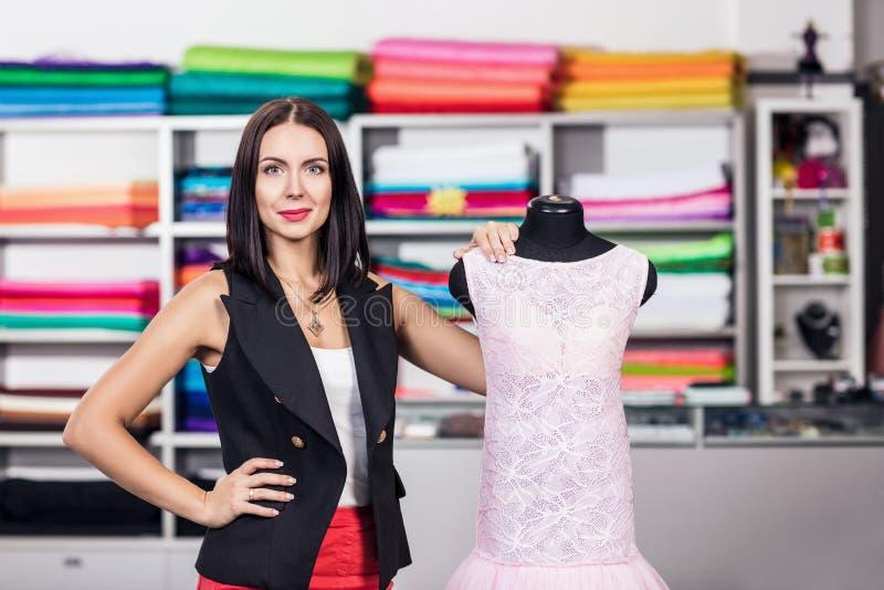 Усмехаясь женщина dressmaker в студии стоковая фотография