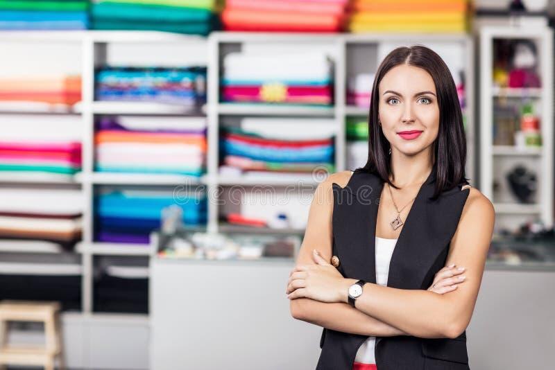 Усмехаясь женщина dressmaker в студии стоковые изображения
